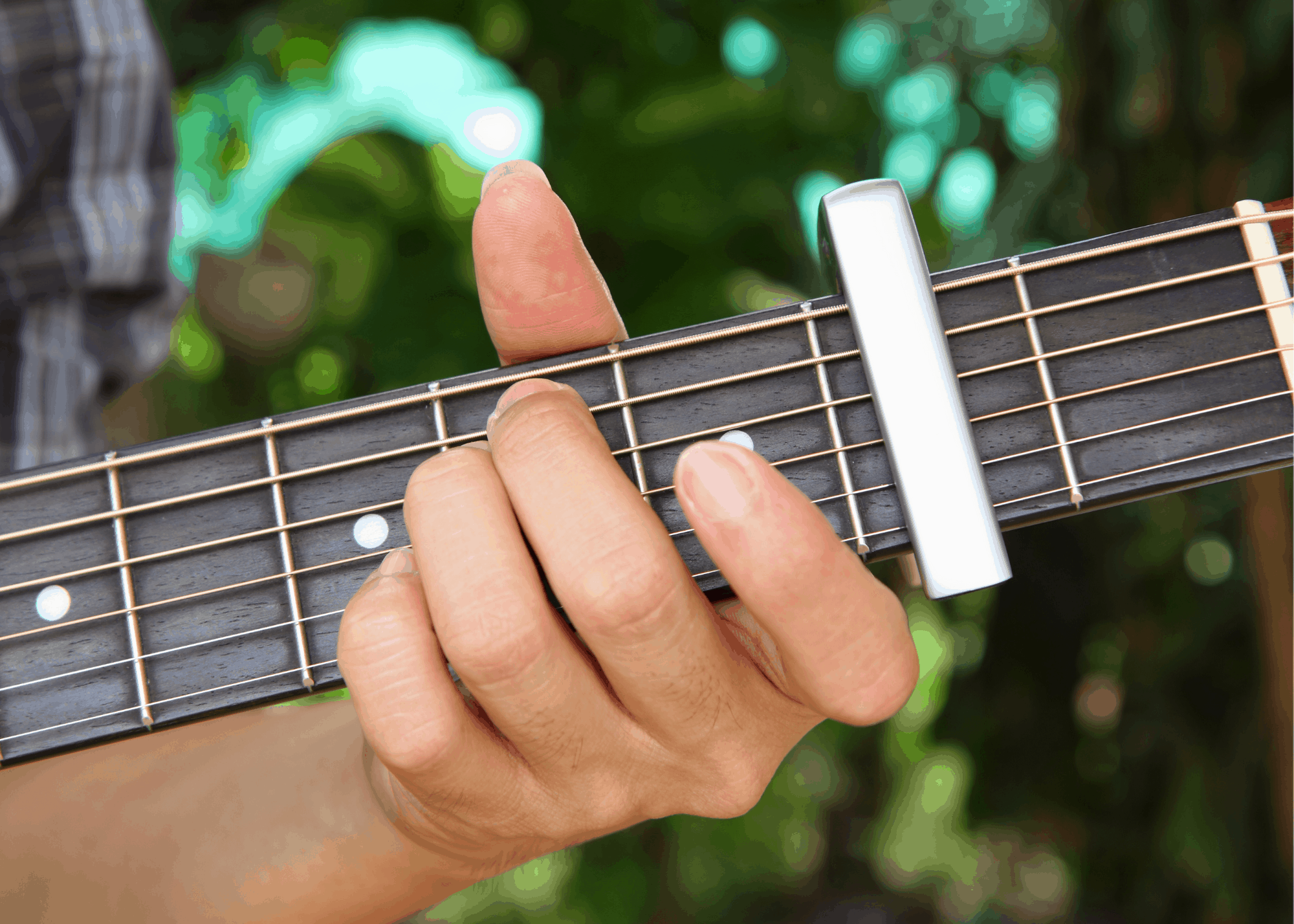 person playing a guitar using a capo